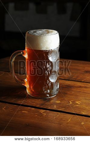 glass of cold  foamy beer on a wooden background