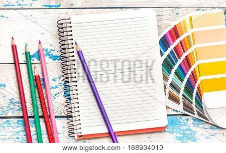 Notepad with color swatches book and colored pencils on the table.