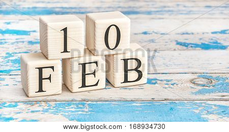February 10th. Wooden cubes with date of 10 February on old blue wooden background.