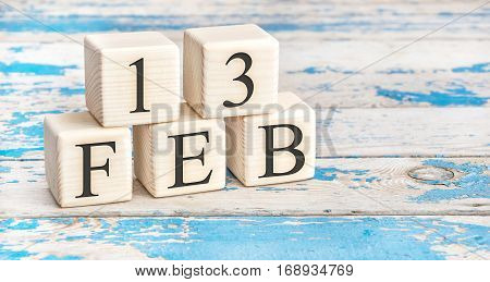 February 13th. Wooden cubes with date of 13 February on old blue wooden background.