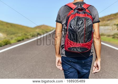 closeup of a young caucasian man seen from behind carrying a backpack walking by a minor road