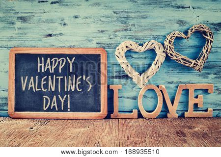 a chalkboard with the text happy valentines day, two heart-shaped ornaments made with natural fibers and some wooden letters forming the word love, against a blue rustic wooden background