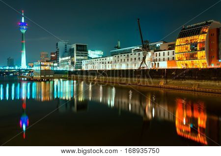Night scene of Rhein river at night in Dusseldorf. View from Media harbor on Rheinturm tower cafe on water and port crane with reflections at water; Night filter
