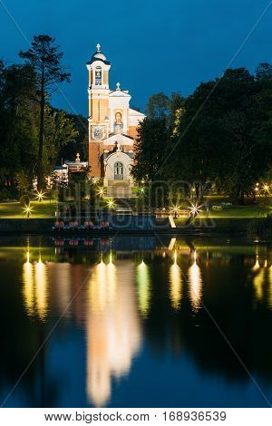 Mir, Belarus. View From Side Of Evening Lake Of Chapel And Burial Vault Of Svyatopolk-Mirsky Family In Bright Illumination. Part Of Architectural Ensemble Of Mir Castle Complex Under Blue Sky.