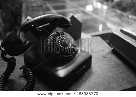 The black old telephone on wooden table.