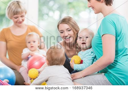 Young women in mother and child group playing with their baby kids