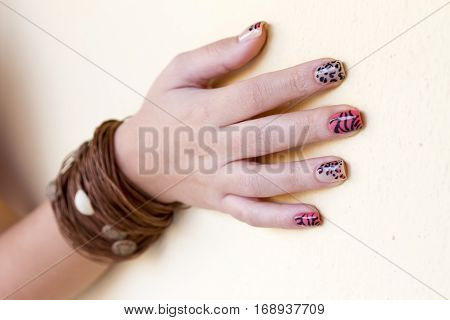 Manicure - Beauty treatment photo of nice manicured woman fingernails. Very interesting nail art with animal print nail polish. Selective focus