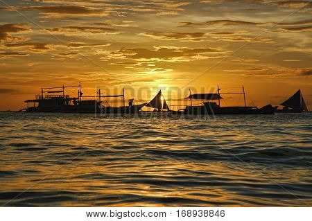 Sailboat Silhouetted Against A Setting Sun