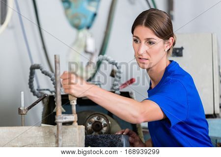 Female stonemason adjusting workpiece in polishing machine