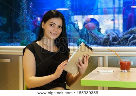 Girl sitting at a cafe looks at photos using a silver digital tablet in the background blue aquarium