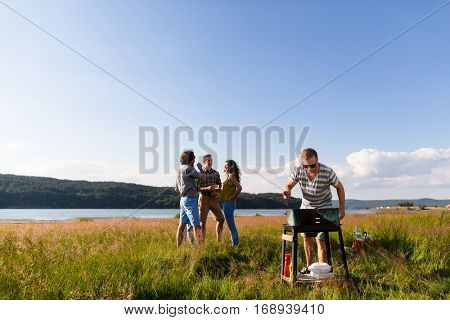 Gang of young men and women having barbecue at lake in summer
