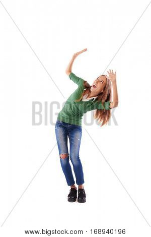 Full-length portrait of surprised girl who kneels and defends with hands under the copy space. Concept for amazement, astonishment