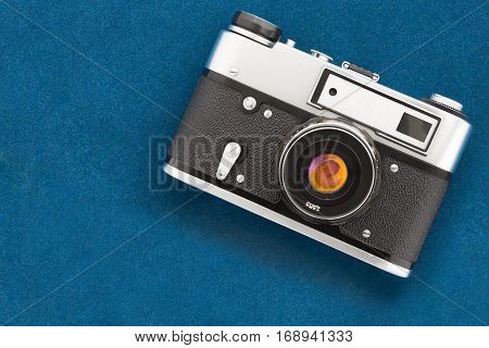 Vintage old-fashioned photo camera lying down on velvet blank background. Top view.