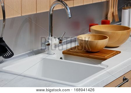 Modern kitchen interior with faucet and sink on foreground.
