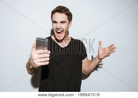 Image of young angry man dressed in black t-shirt standing over white background and using phone.