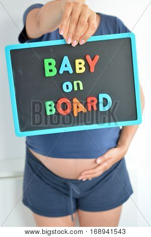 Pregnant woman holds a baby on board colored text on blackboard over her belly