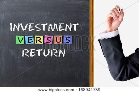 Investment versus return text on blackboard, conceptual