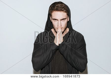 Photo of young man dressed in black t-shirt and mantle standing over white background and prays.