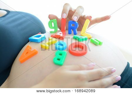 Young expectant mother with letter blocks spelling girl on her pregnant belly