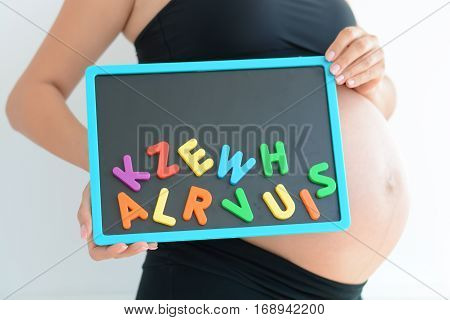 Young expectant mother with magnetic letter blocks trying to pick a name for her baby.
