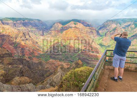 Tourist taking pictures  of the beautiful views in Waimea Canyon lookout, Kauai island, Hawaii