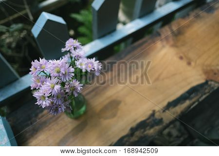 Purple flower in a glass on wooden table.