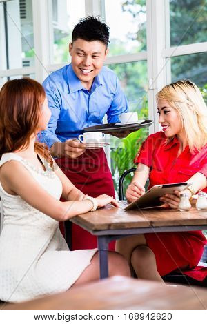 Friendly smiling waiter serving two attractive stylish ladies coffee in an Asian restaurant
