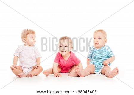 Group of witty babies sitting in different clothes, isolated on white background