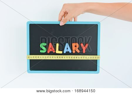 Measure salary concept in a business, company or economy with colorful magnetic letters on blackboard