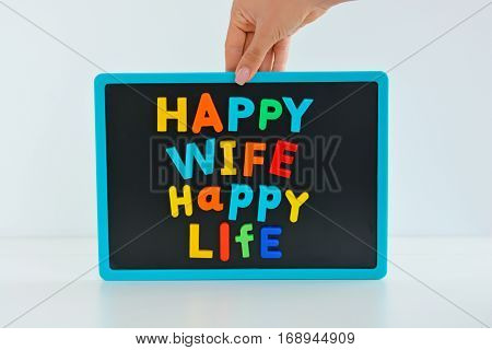 Happy wife happy life with magnetic colored letter blocks on blackboard