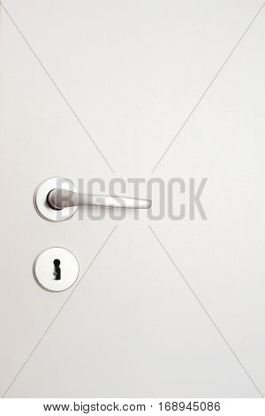 White closed door with silver doorknob on white wall background