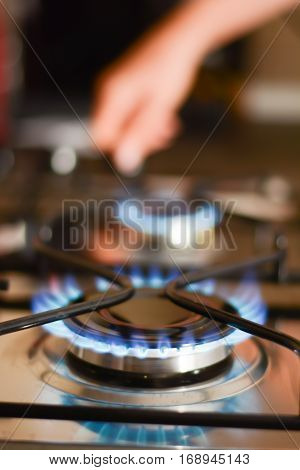 Woman turning on the fire of a gas stove