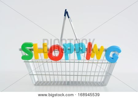 Metal Shopping basket with magnetic letters on it spelling the word shopping