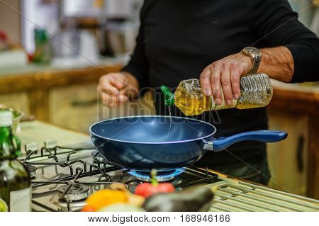 Chef in restaurant kitchen at stove with pan adding oil.