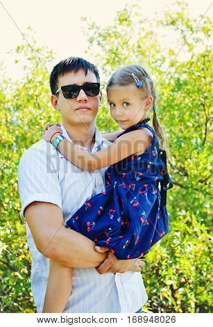 father is holding sweet little daughter outdoors