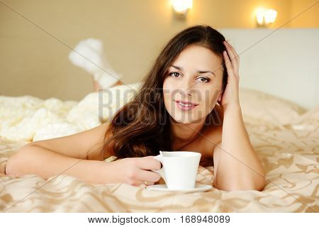 pretty brunette enjoying coffee in the bed