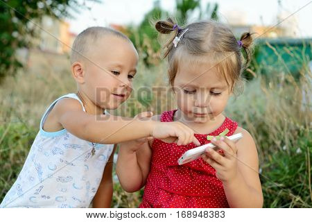 boy and girl are playing phone outdoors