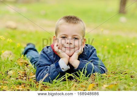 little boy lying on the meadow in fall