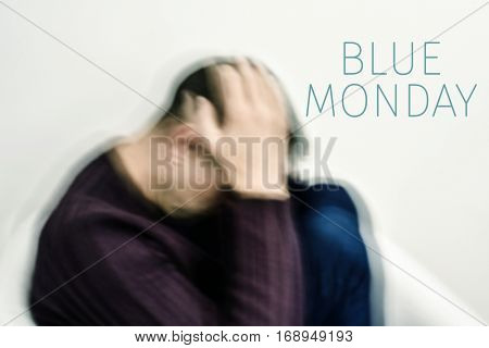 closeup of a blurred young caucasian man curled up with his hands in his head and the text blue monday