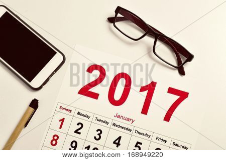 high-angle shot of a 2017 calendar, a pair of eyeglasses, a smartphone and a pen on a white office desk