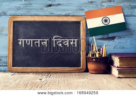 a chalkboard with the text Republic Day written in Hindi and a flag of India, on a rustic wooden surface, against a blue wooden background