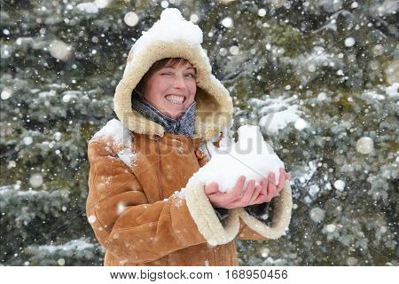beautiful woman play with snow on winter outdoor, snowy fir trees in forest, wearing a sheepskin coat