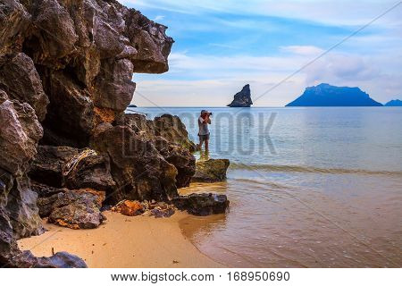 Rest of the Andaman Sea. The islands - rocks in shallow water. Photographer in striped T-shirt takes seascape