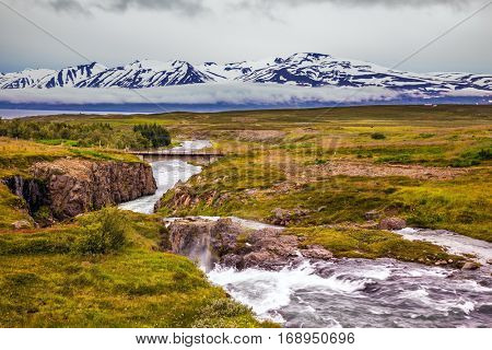The rapid cold creek flows among the flat tundra. On the horizon - rhyolite mountains in the snow.  The concept of extreme northern tourism