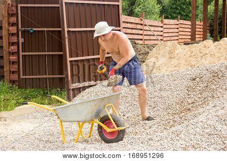 Man Loading Gravel Into Wheelbarrow With A Shovel