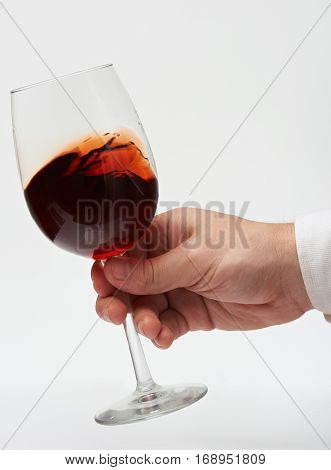 Moving red wine in stem glass isolated on white background. Test red wine. Close up of drinking red wine