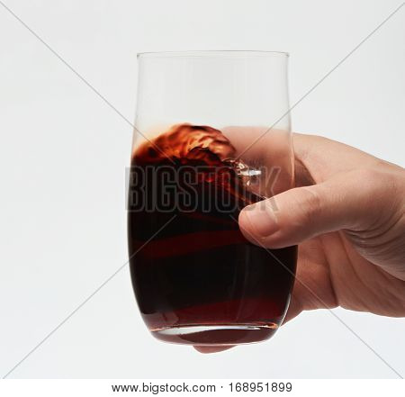 Close up of red wine in stemless glass isolated on white background. Testing red wine. Move red wine