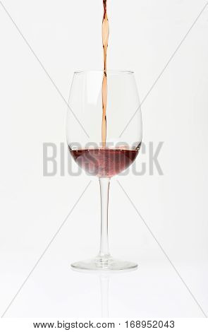 Pouring red wine in to glass. Glass half full with red wine. Vertical pouring wine