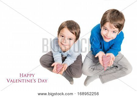 Two brothers holding heart in hands. Isolated on a white background