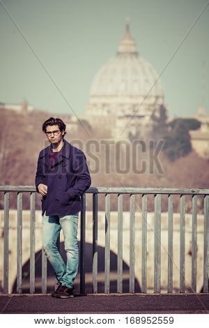 Trendy handsome young boy leaning on the railing of a bridge in the historic center of Rome in Italy. Wearing a jacket and jeans, eyeglasses and has a phone in hand. Behind him the majestic basilica of Saint Peter.